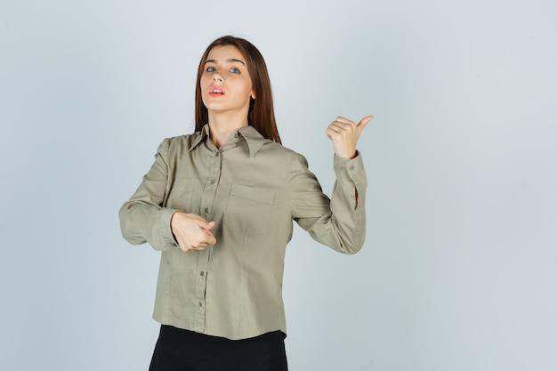 Młoda kobieta wskazuje na bok z kciukami w koszuli, spódnicy i patrząc niezdecydowany