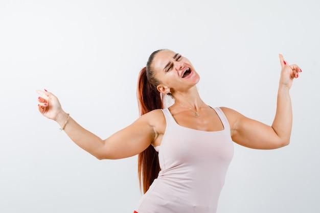Młoda kobieta wskazuje na boki w podkoszulku i wygląda szalenie, widok z przodu.