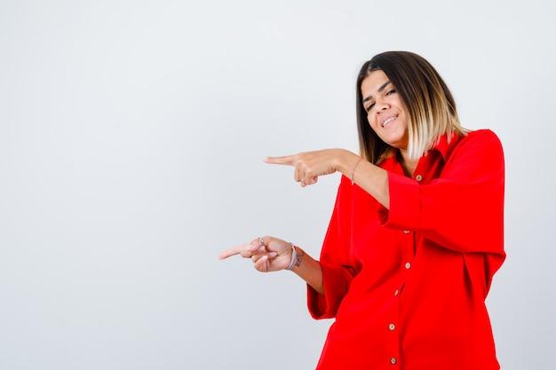 Młoda kobieta wskazuje na lewą stronę w czerwonej koszuli oversize i wygląda na szczęśliwą. przedni widok.