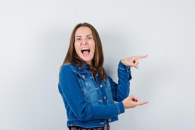 Młoda kobieta wskazuje na prawą stronę, otwiera usta w dżinsowej kurtce, sukience i wygląda na wściekłą. przedni widok.