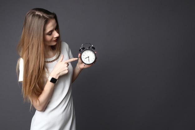 Młoda kobieta wskazuje na retro budzik
