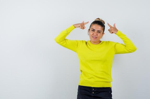 Młoda kobieta wskazuje na siebie palcami wskazującymi w żółtym swetrze i czarnych spodniach i wygląda poważnie