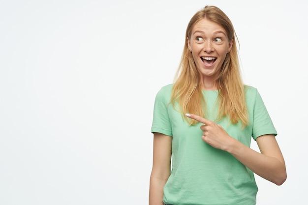 Młoda kobieta wskazuje palcem w przestrzeń kopii ze zdumionym, szczęśliwym wyrazem twarzy