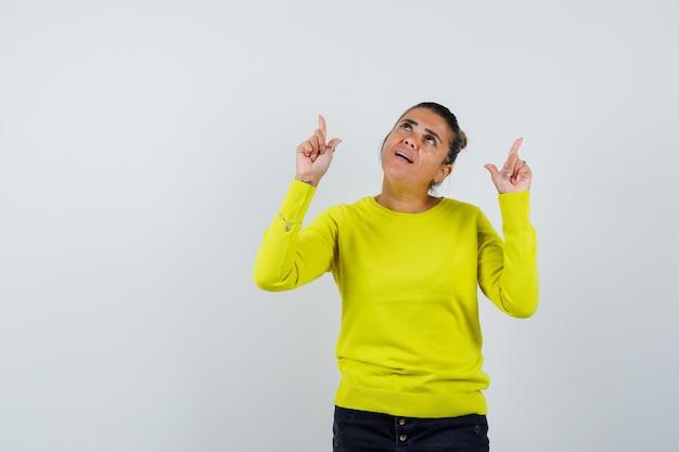 Młoda kobieta wskazuje palcem wskazującym w żółtym swetrze i czarnych spodniach i wygląda na skupioną