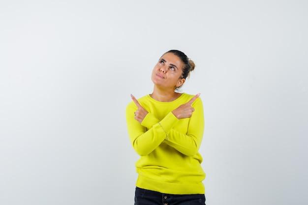 Młoda kobieta wskazuje przeciwne kierunki w żółtym swetrze i czarnych dżinsach i wygląda na skupioną