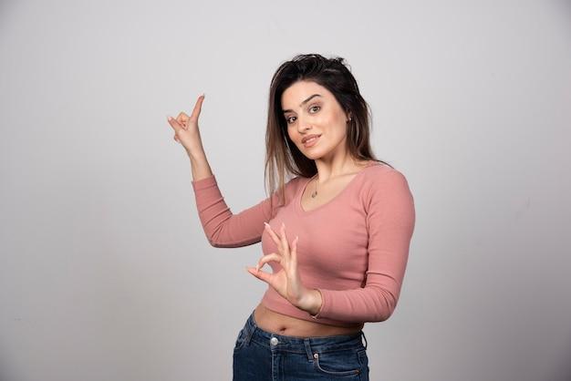 Młoda kobieta wskazuje w górę i pokazuje ok gest.