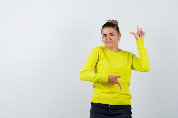 Młoda kobieta wskazuje w górę iw dół w żółtym swetrze i czarnych spodniach i wygląda na szczęśliwą