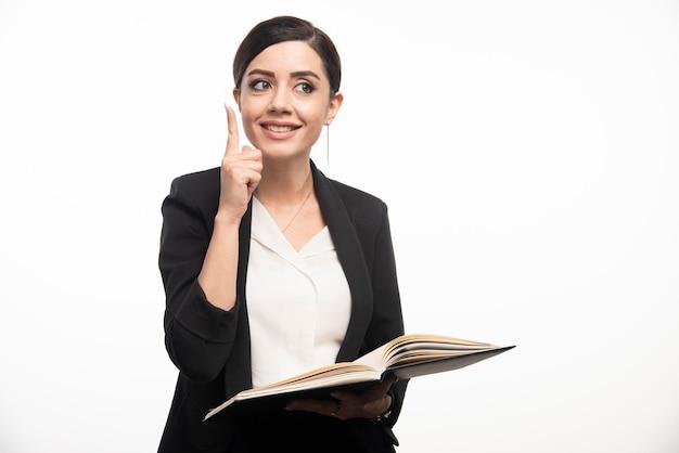 Młoda kobieta wskazuje w górę strony na białym tle. zdjęcie wysokiej jakości