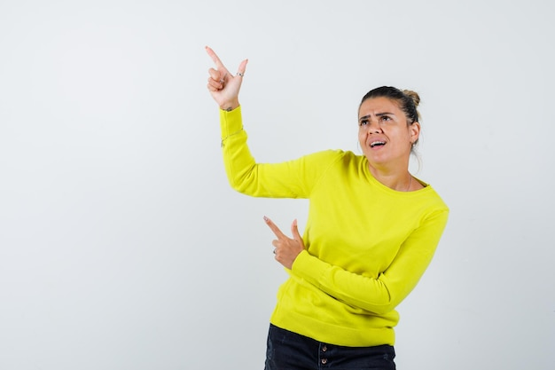 Młoda kobieta wskazuje w górę w żółtym swetrze i czarnych spodniach i wygląda na skupioną