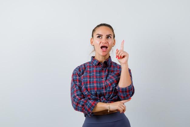 Młoda kobieta wskazuje w kratkę koszulę, spodnie i patrząc zdziwiony. przedni widok.
