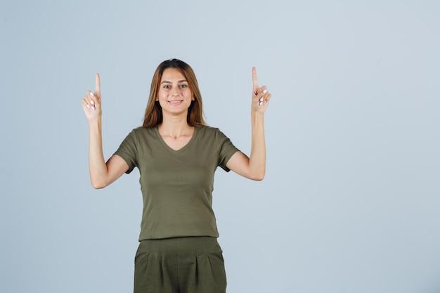 Młoda kobieta wskazuje w t-shirt, spodnie i wygląda na szczęśliwego. przedni widok.