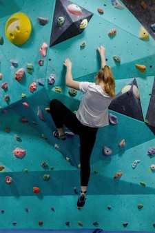 Młoda kobieta wspina się na ścianie ćwiczeń w siłowni