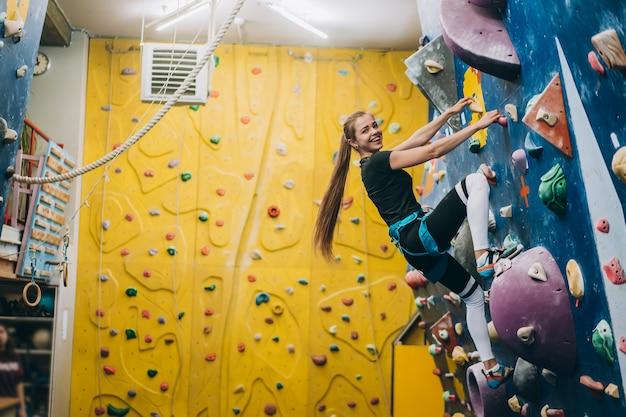 Młoda kobieta wspinająca się po wysokiej, sztucznej ścianie wspinaczkowej wykonanej przez człowieka