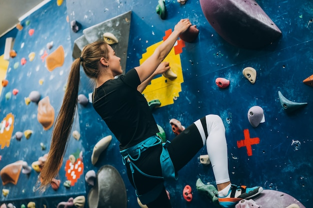 Młoda kobieta wspinająca się po wysokiej, sztucznej sztucznej skalnej ścianie wspinaczkowej