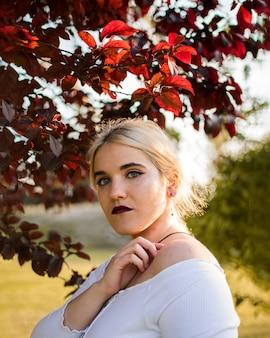 Młoda kobieta wśród jesień liści podczas zmierzchu
