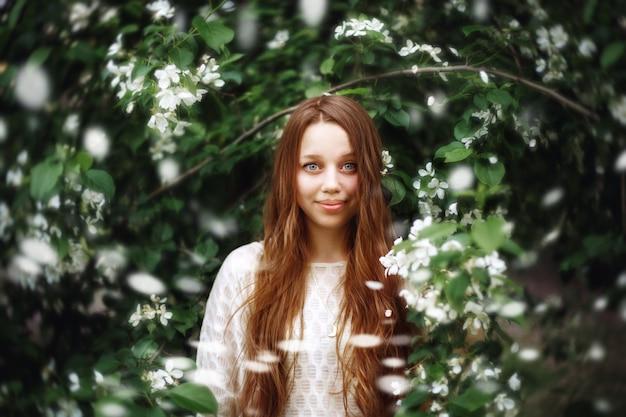 Młoda kobieta wśród wiosennych kwiatów na zewnątrz