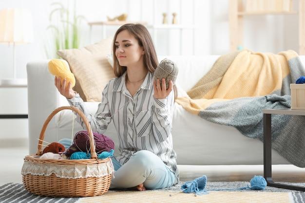 Młoda kobieta wybiera kolor nici dziewiarskich w domu