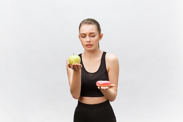 Młoda kobieta wybiera między deserem a jabłkiem dieta koncepcja żywności.