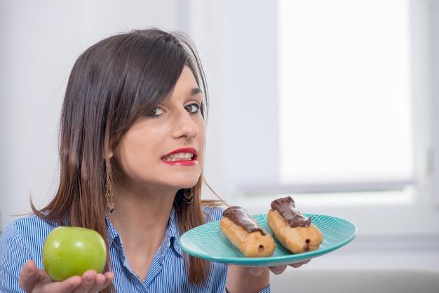 Młoda kobieta wybiera między jabłkiem i czekoladowym ciastem