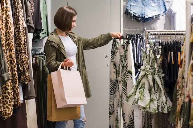 Młoda kobieta wybiera różnych stroje