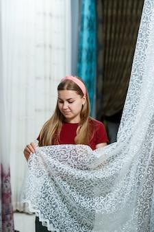 Młoda kobieta wybiera tkaninę na nowe zasłony w sklepie. próbki zasłony wiszą w sklepie na wieszakach na szynie. próbki faktur tkanin, tiulu i tapicerki meblowej.