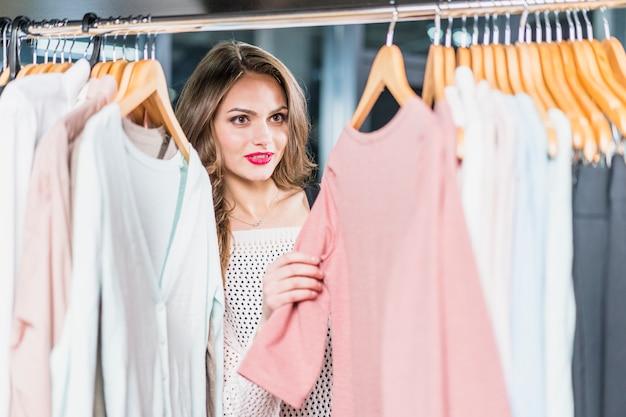 Młoda kobieta wybiera ubrania na stojaku w salonie