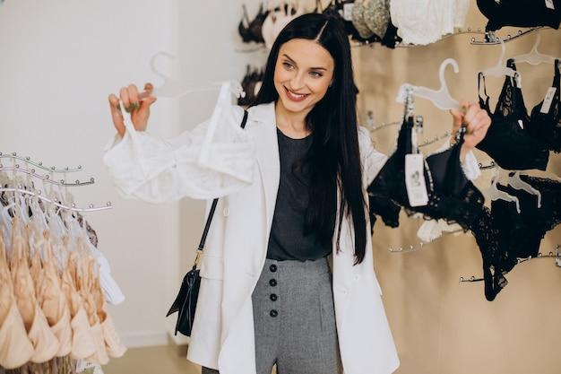 Młoda kobieta wybierająca bieliznę w centrum handlowym