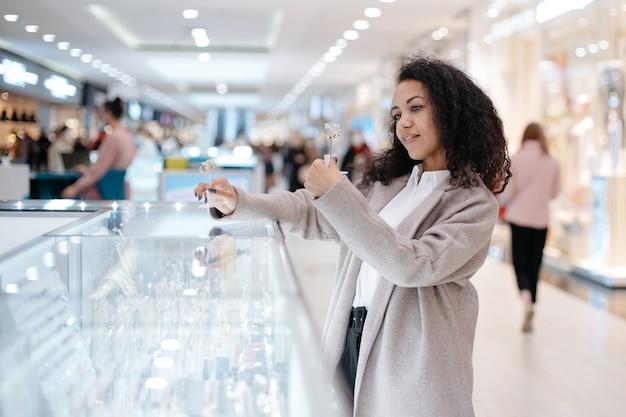 Młoda kobieta wybierająca biżuterię w sklepie jubilerskim
