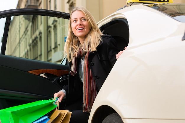 Młoda kobieta wychodzi z taksówki