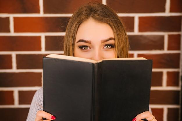 Młoda kobieta wychodzi zza książki. piękne oczy patrzą w obiektyw. okładka w twardej oprawie.