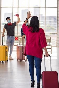 Młoda kobieta wyciąga bagaż i macha ręką do przyjaciół z maską na terminalu odlotów lotniska. dziewczyna witająca się z towarzyszem.
