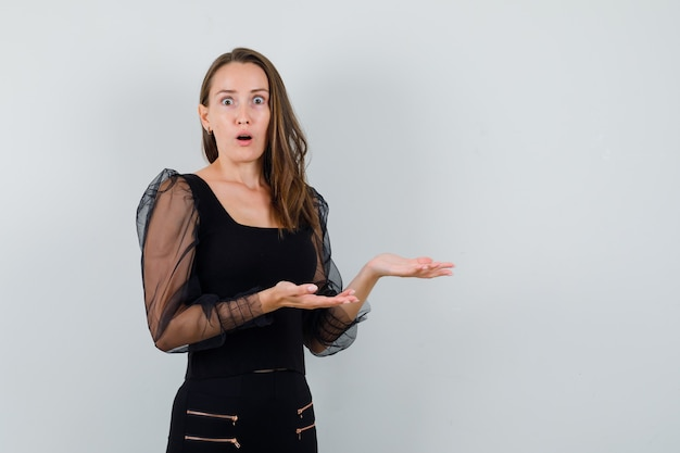 Młoda kobieta wyciąga ręce, by otrzymać coś w czarnej bluzce i czarnych spodniach i wygląda na zszokowaną, widok z przodu.