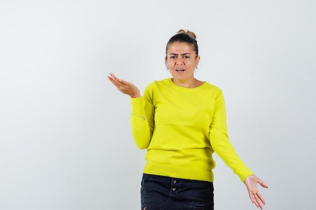 Młoda kobieta wyciąga ręce w pytający sposób w żółtym swetrze i czarnych spodniach i wygląda na zakłopotaną