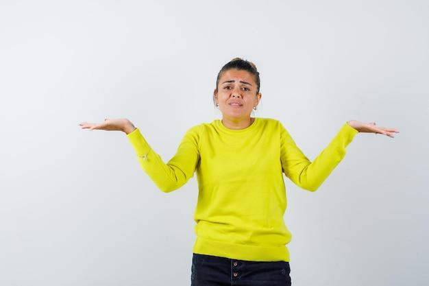 Młoda kobieta wyciąga ręce w pytający sposób w żółtym swetrze i czarnych spodniach i wygląda na zdziwioną