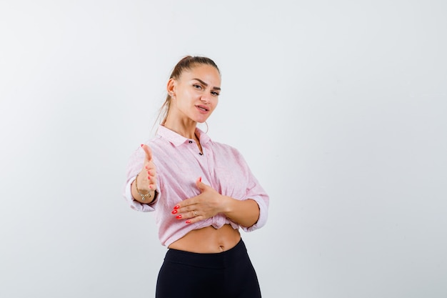 Młoda kobieta wyciąga rękę do aparatu w koszuli i wygląda pewnie. przedni widok.