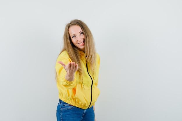 Młoda kobieta wyciąga rękę do kamery w żółtej bomberce i dżinsach, patrząc na szczęśliwą. przedni widok.