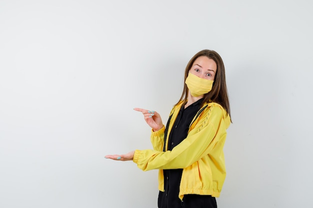 Młoda kobieta wyciąga rękę, jakby coś trzyma