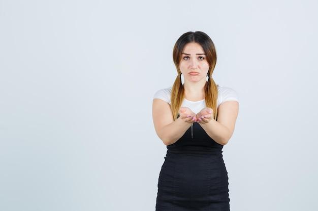 Młoda kobieta wyciąga złożone dłonie i wygląda na rozczarowaną