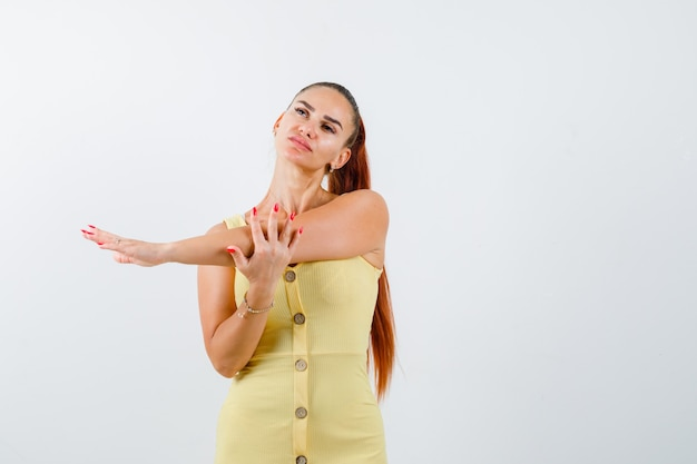 Młoda kobieta, wyciągając ramiona, patrząc w żółtą sukienkę i zamyślony. przedni widok.
