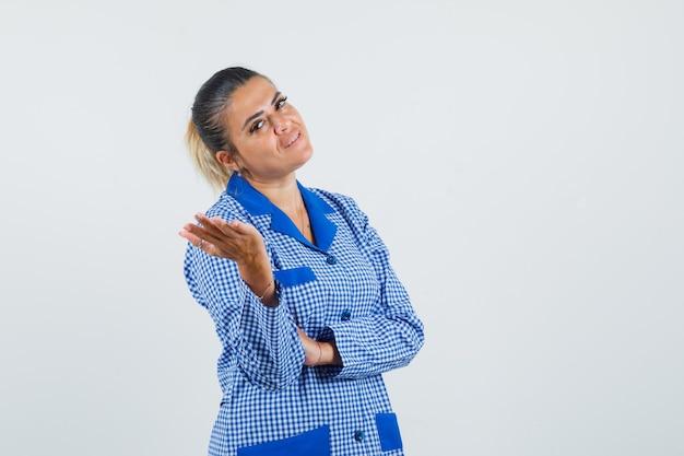 Młoda kobieta, wyciągając rękę w kierunku aparatu w niebieską bawełnianą kratkę piżamy i ładnie wygląda. przedni widok.