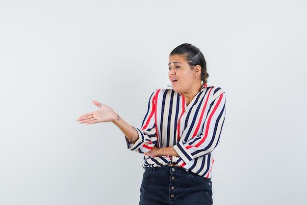 Młoda kobieta wyciągająca ręce w lewo i rozmawiająca z kimś w bluzce w paski i wyglądająca na zaciekawioną.