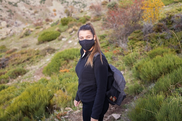 Młoda kobieta wycieczkowicz chodzenie po górach podczas