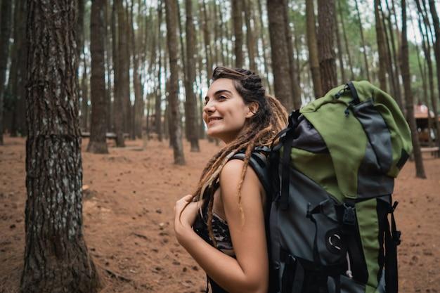 Młoda kobieta wycieczkowicz cieszy się trekking w lesie