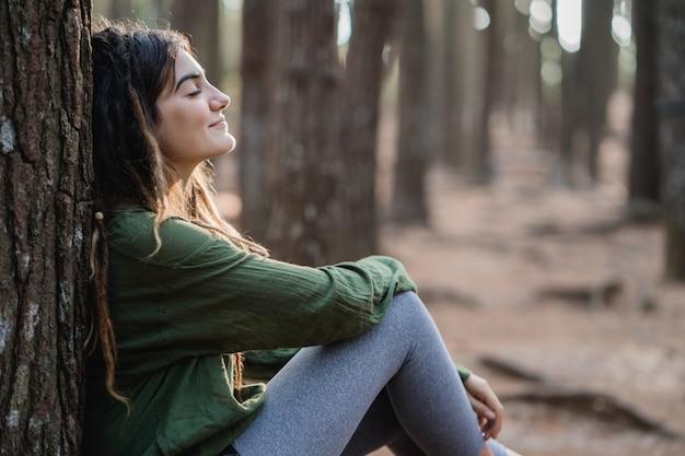 Młoda kobieta wycieczkowicz relaksuje w drewnach