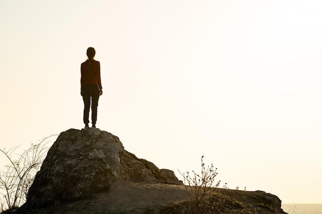 Młoda kobieta wycieczkowicz stoi samotnie na dużym kamieniu w ranek górach. żeński turysta na wysokiej skale w dzikiej naturze.