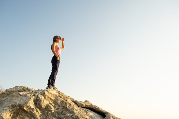Młoda kobieta wycieczkowicz stoi samotnie na dużym kamieniu w ranek górach