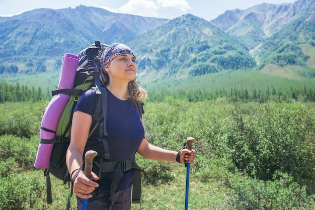 Młoda kobieta wycieczkowicz z plecakiem i trekkingowymi kijami w słoneczny dzień na halnym śladzie