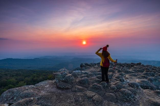 Młoda kobieta wycieczkuje w górach.