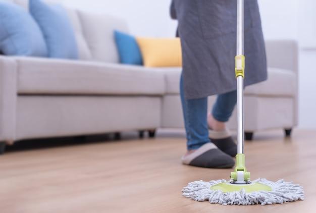 Młoda kobieta wyciera drewniane podłogi w domu mopem