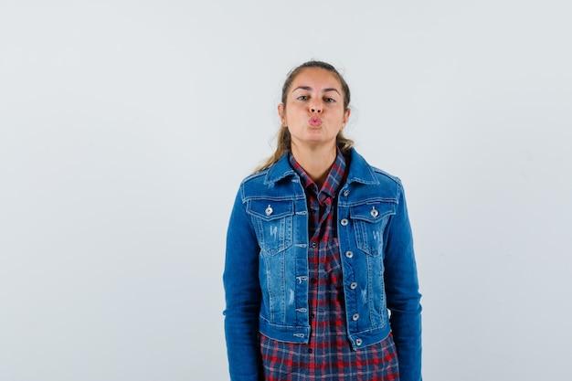 Młoda kobieta wydymając wargi w koszuli, kurtce i patrząc zniewalająco, widok z przodu.
